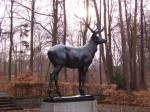 Die Skulptur Bronzener Hirsch steht im Wald.s